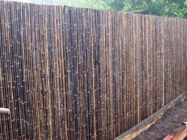 Oude schutting opnieuw bekleed met bamboerollen