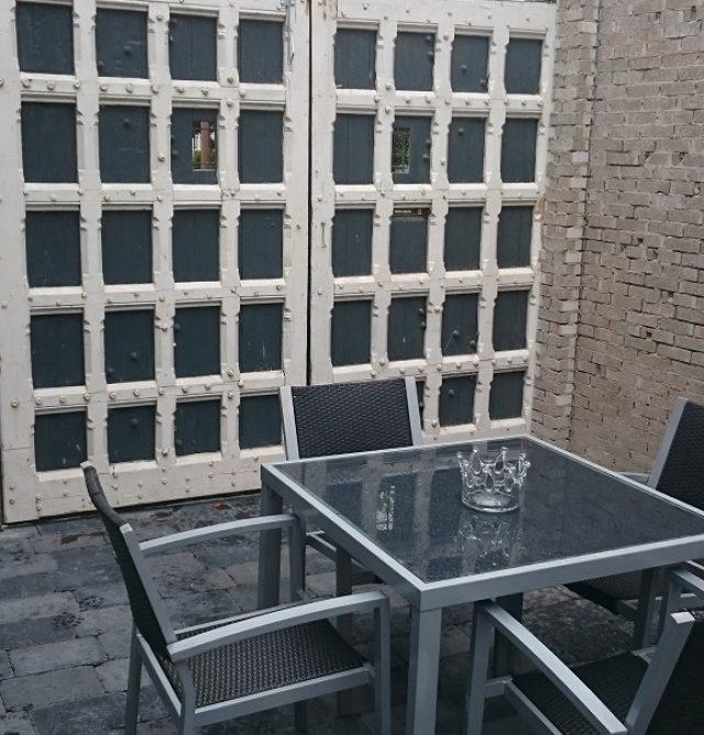 Specialist in de aanleg van bijzondere terrassen. (Hier met authentieke kasteeldeuren.)